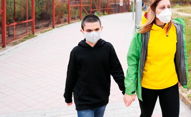 路上で息子と一緒に歩く母 Premium写真