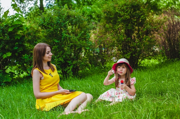 Mother watching as her daughter blows soap bubbles Free Photo