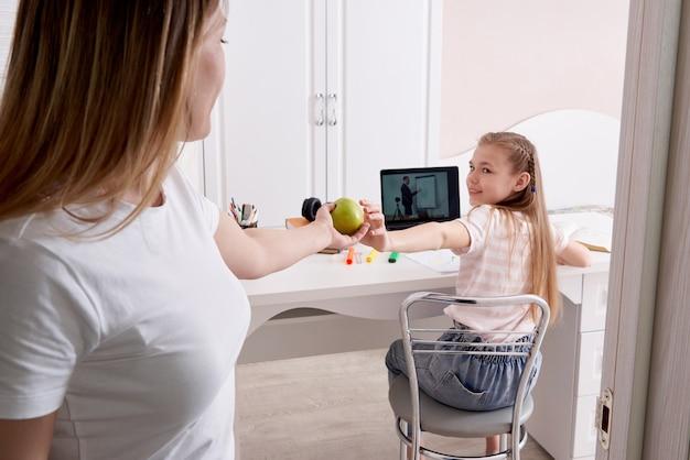 Мать смотрит, как ее дочь делает домашнее задание на ноутбуке дома, входя в комнату и давая зеленое яблоко Premium Фотографии