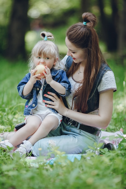 Mother watching her daughter while eating an apple Free Photo