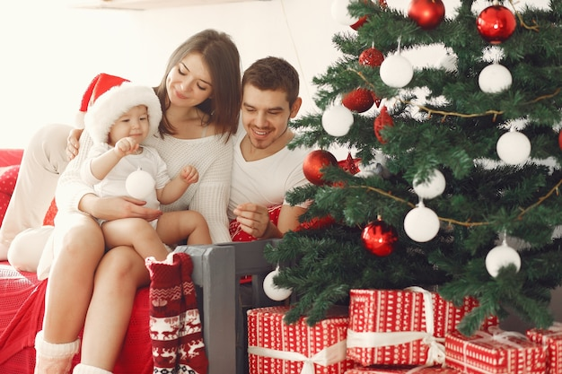 Madre in un maglione bianco. famiglia con regali di natale. bambino con i genitori in decorazioni natalizie. Foto Gratuite