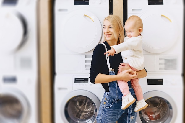Mother with baby on the background of washing machines Premium Photo