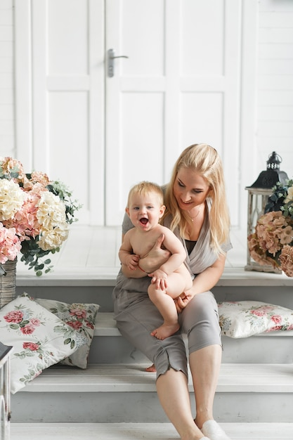 Mother with baby play in studio decorated flowers Free Photo