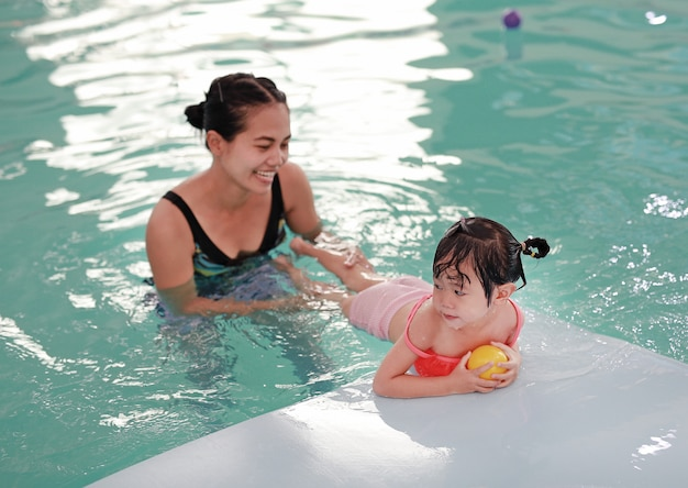 Mother with baby in swimming pool training Premium Photo