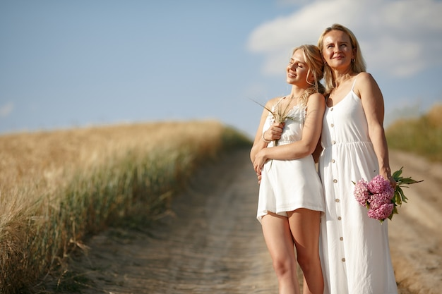 Mother with beautiful daughter in a autumn field Free Photo