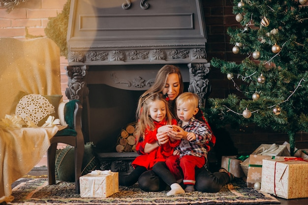Mother with children by christmas tree Free Photo