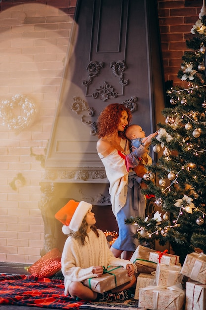 Mother with children decorating christmas tree Free Photo