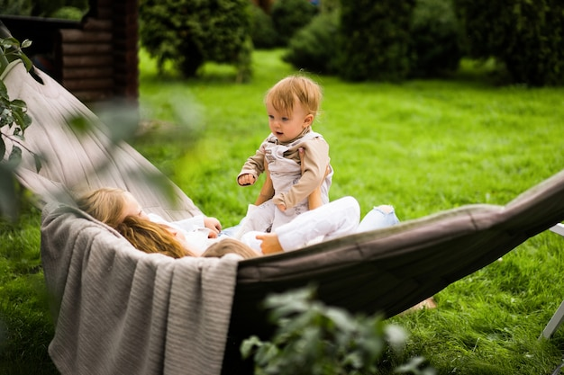 Mother with children having fun in a hammock. mom and kids in a hammock. Free Photo