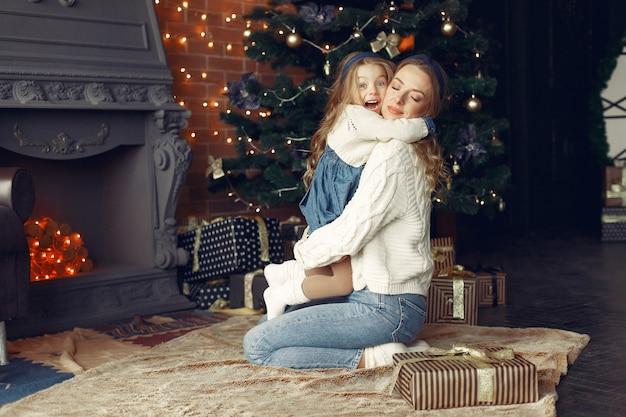 벽난로 근처 집에서 귀여운 딸과 어머니 무료 사진