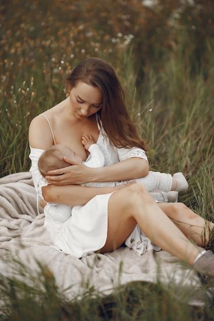 Madre con figlia carina. mamma che allatta la sua piccola figlia. donna in abito bianco. Foto Gratuite