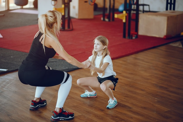 Mother with cute daughter play sports in the gym Free Photo