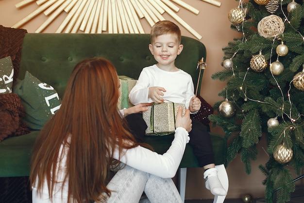 クリスマスツリーの近くのかわいい息子を持つ母 無料写真