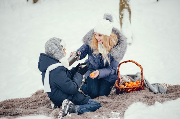 Mother with cute son in a winter oark Free Photo