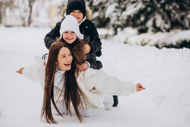 딸과 아들이 눈이 가득한 공원에서 재미와 어머니 무료 사진