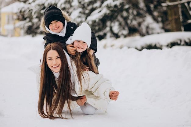 Мать с дочерью и сыном весело в парке, полном снега Бесплатные Фотографии
