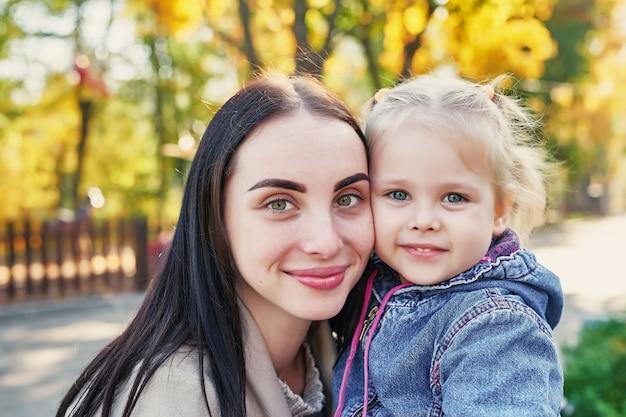 Mother with daughter in autumn park Premium Photo