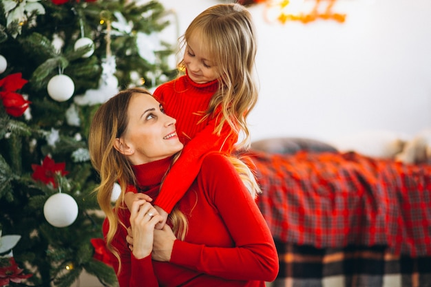 Mother with daughter by christmas tree Free Photo
