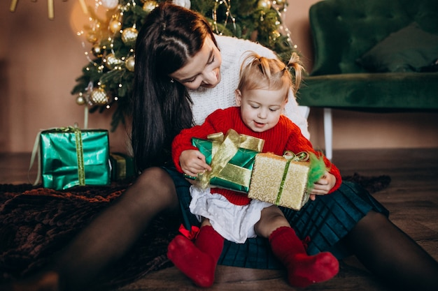 Mother with daughter by the christmas tree Free Photo