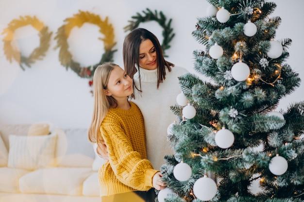 크리스마스 트리를 장식하는 딸과 어머니 무료 사진
