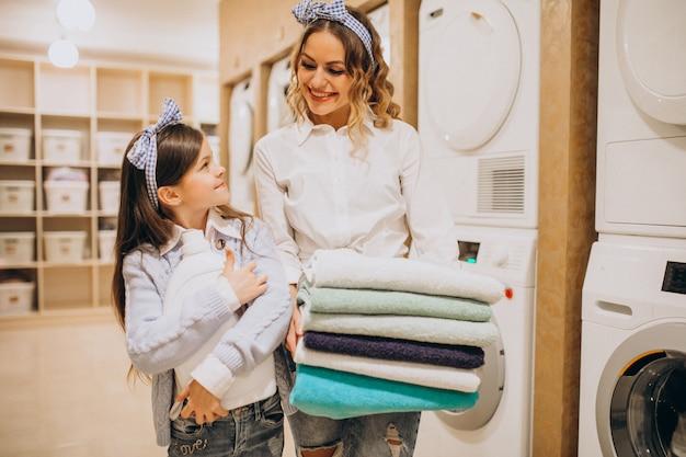 セルフサービスコインランドリーで洗濯をしている娘を持つ母 無料写真