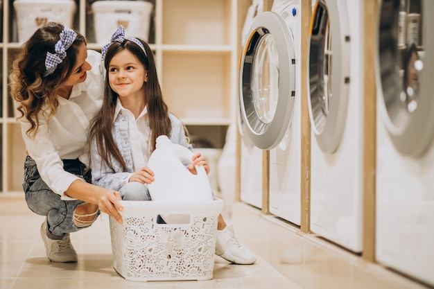 Mother with daughter doing laundry at self serviece laundrette Free Photo