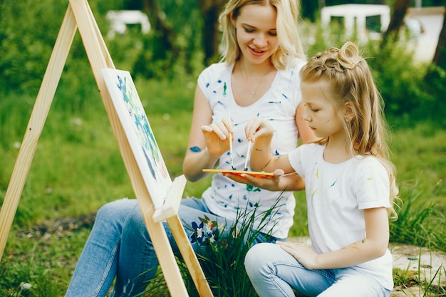 Mother with daughter drawing in a park Free Photo