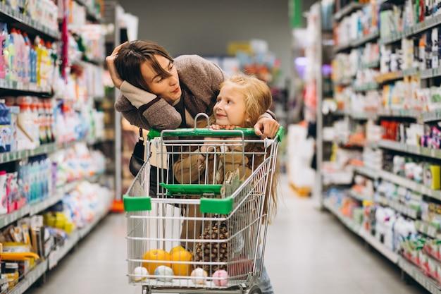 Madre con figlia in un negozio di alimentari Foto Gratuite