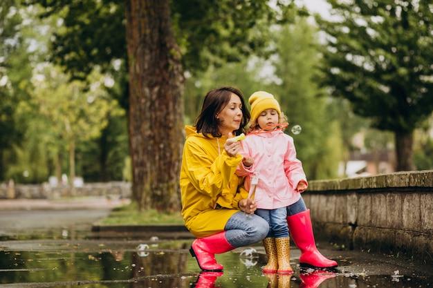 雨の日の公園で楽しんでいる娘を持つ母 無料写真
