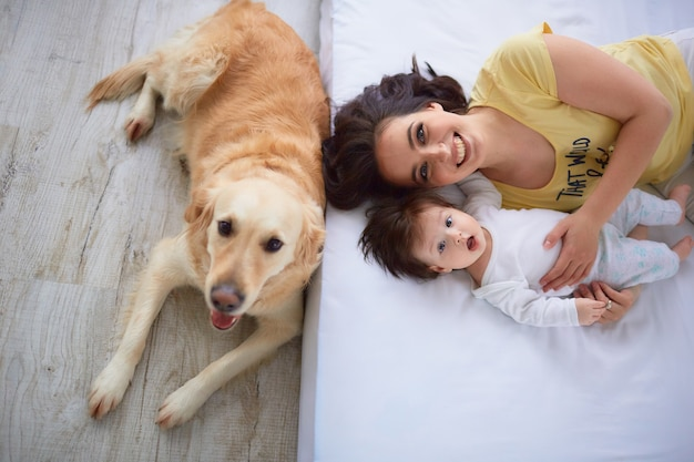 The mother with daughter lie on the bed and dog sitting near bed Free Photo