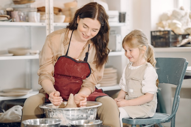 Mother with daughter makes vase in a potterystudio Free Photo