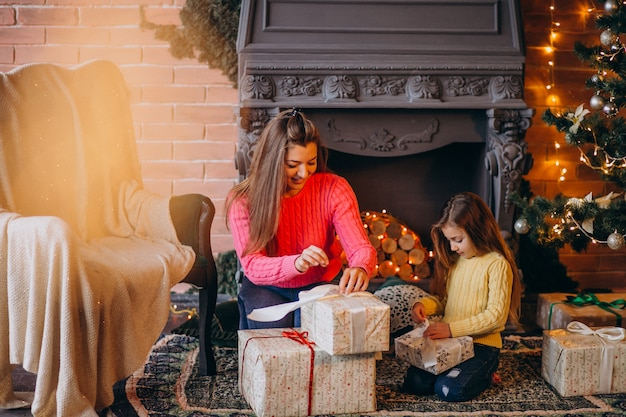 Mother with daughter packing present by fireplace on christmas Free Photo