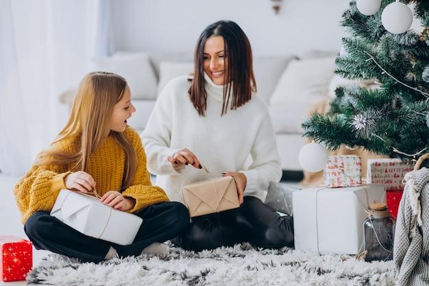 Madre con i regali dell'imballaggio della figlia sotto l'albero di natale Foto Gratuite