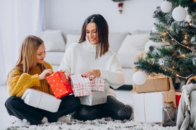 크리스마스 트리 아래 선물 포장 딸과 어머니 무료 사진