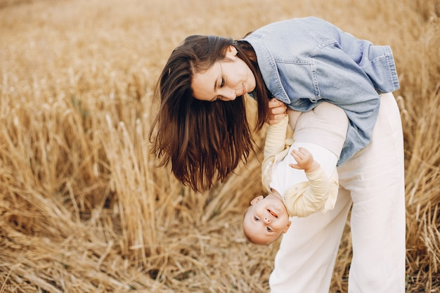 Mother with daughter playing in an autumn field Free Photo