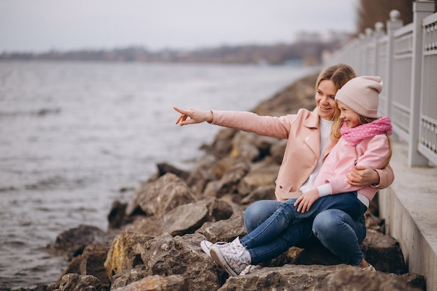 Mother with daughter sitting by the lake Free Photo