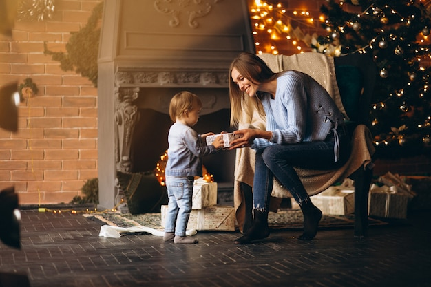 Mother with daughter sitting in chair by christmas tree Free Photo