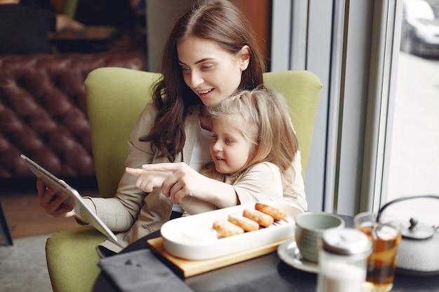 カフェに座っている娘を持つ母 無料写真