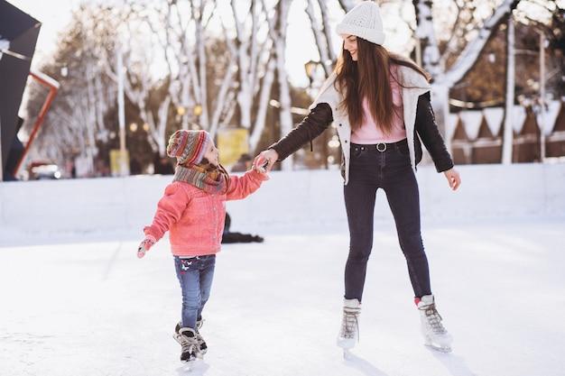 Madre con il pattinaggio su ghiaccio d'istruzione della figlia su una pista di pattinaggio Foto Gratuite
