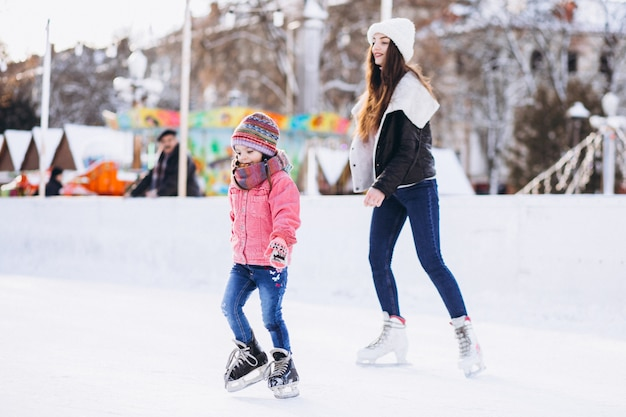 Mother with daughter teaching ice skating on a rink Free Photo
