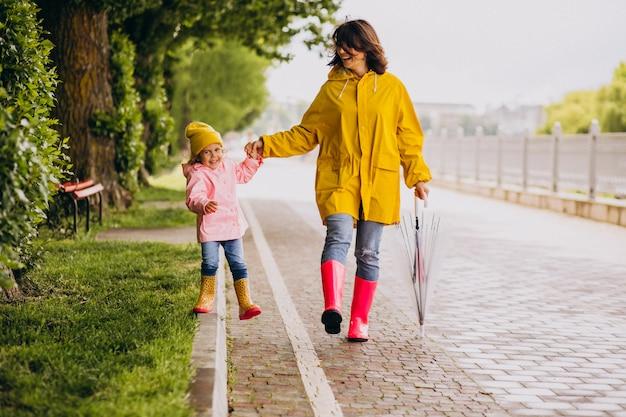 ゴム長靴を着て雨の中で公園を歩いて娘を持つ母 無料写真