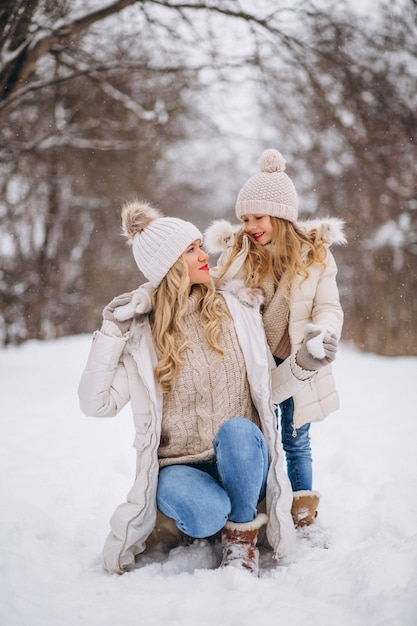 Mother with daughter walking together in a winter park Free Photo