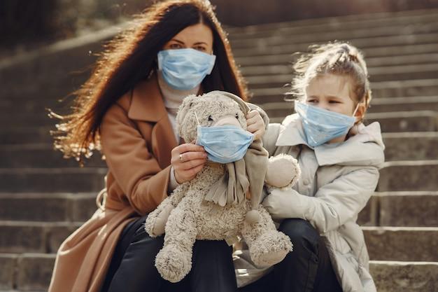 La madre con la figlia cammina fuori in maschere Foto Gratuite