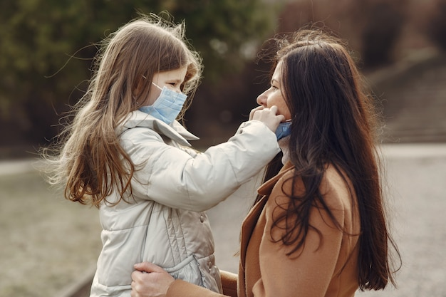 Mother with daughter walks outside in masks Free Photo
