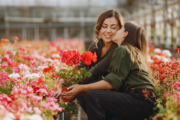 Mother with daughter. workers with flowerpoots. girl in a green shirt Free Photo