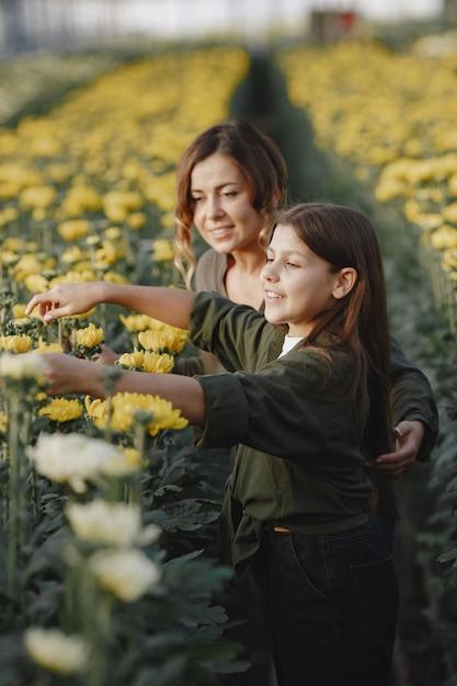 娘と母。フラワープートを持つ労働者。緑のシャツを着た女の子 無料写真