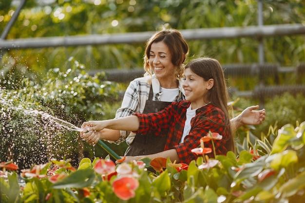 Мать с дочерью. рабочие с цветочными горшками. люди льют цветы Бесплатные Фотографии