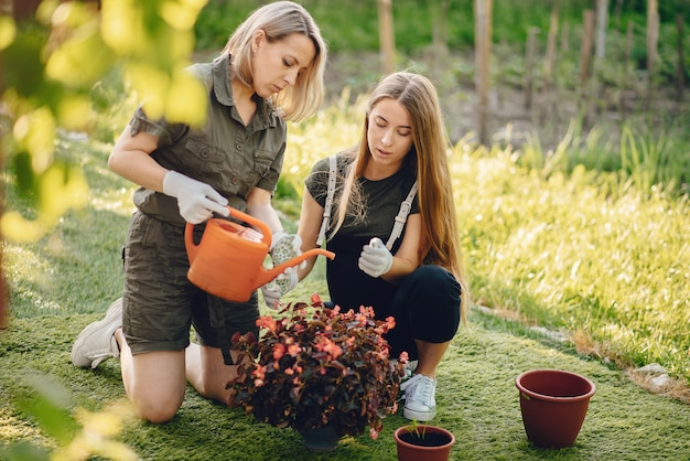 Mother with a daughter works in a garden near the house Free Photo