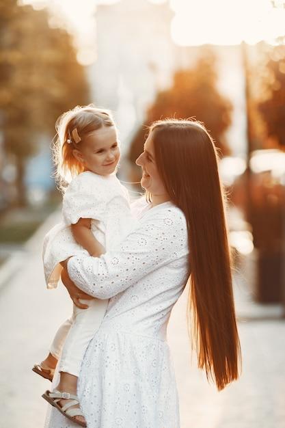 娘が遊んでいるお母さん。白いドレスを着た女性。夕日を背景に家族。 無料写真