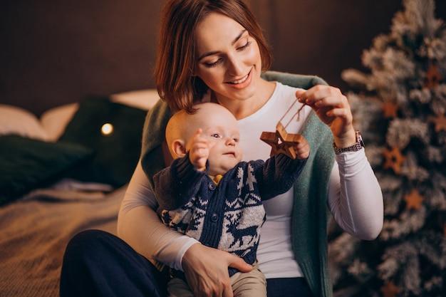 크리스마스를 축 하하는 그녀의 아기와 엄마 무료 사진