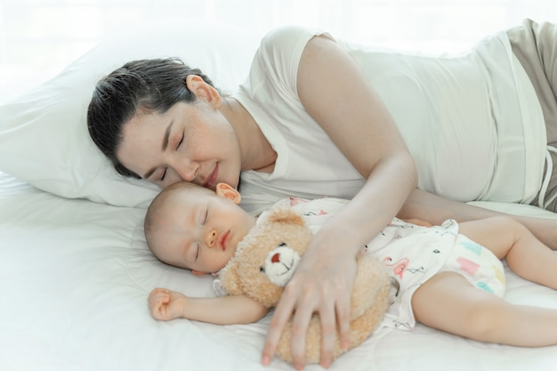Mother with her baby sleeping on bedroom Free Photo